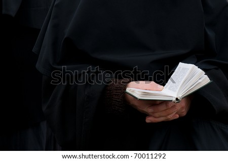 a hand of a praying nun holding Holy Bible against her dark clothes