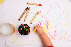 A hand of baby drawing lines and shapes with colorful crayons.