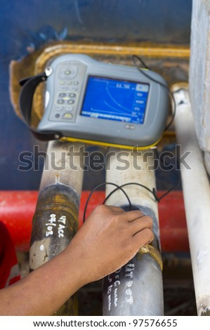 a hand of worker checking quality of weld using industrial ultrasonic device