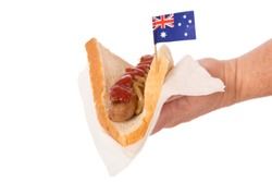 A hand offering a sausage sizzle, traditional Australian food.