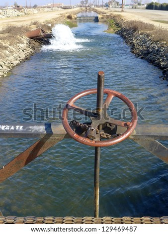 A hand operated wheel controls a sluice gate on a Central California irrigation canal