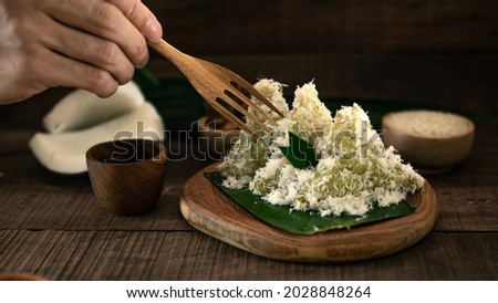 A hand picking up Lupis using wooden fork. Lupis is an Indonesian traditional cake made of glutinous rice topped with shredded coconut served with thick palm sugar syrup.  Zdjęcia stock ©