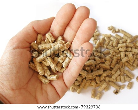 A hand picking wood pellets