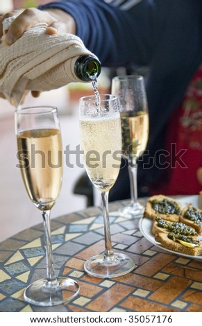 A hand pouring champagne into glass