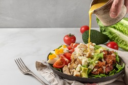 A hand pouring salad dressing into cobb salad with chicken, avocado, bacon, blue cheese, tomato and eggs. Keto diet food. Classic American dish
