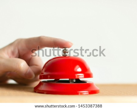 A hand press the red handbell on wooden table on white background; selected focus at the index finger that pressing the bell button. concept of calling for assistance. #1453387388