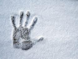 A hand print on fresh snow. Virtual greeting.