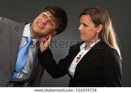 a hand pulling a businessman ear on gray