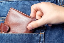 A hand pulls a wallet out of the back pocket of his jeans.The concept of pickpocketing or theft in the family from parents.