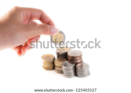 A hand put a coin into stack of coins