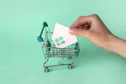 A hand puts a paper white house in a mini shopping trolley on a green background. The concept of buying or renting a house, apartment, cottage and much more.