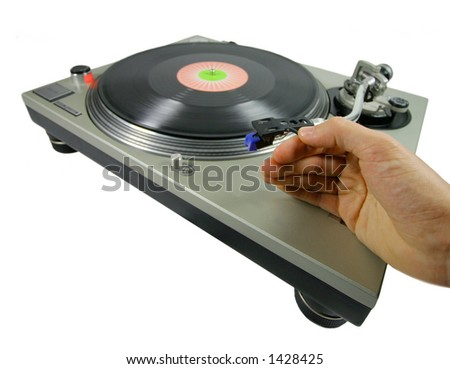 a hand putting a needle on a record - stock photo