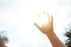 a hand reaches for the sky and covers the sun, the sun's rays make their way through the hand, close - up
