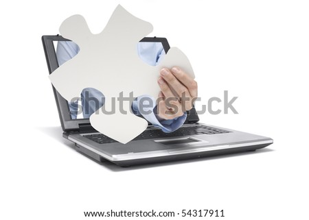 a hand reaches out of a laptop with pieces of puzzle