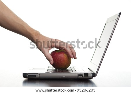 A hand reaching out and taking an apple from a laptop keyboard.