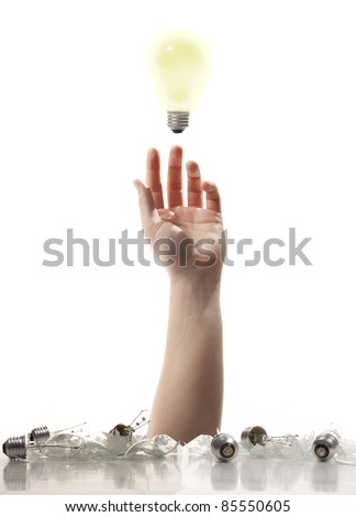 A Hand reaching up from a pile of broken light bulbs trying to grab that one good idea.