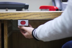 A hand ready to press a panic button under an administrative desk