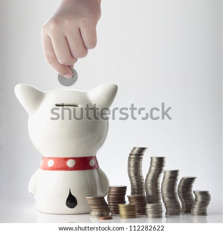 a hand saving coin in piggy bank on white background