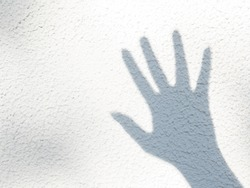 A hand shadow on white wall. Palm silhouette with outstretched fingers as a symbol of greeting. Grey cement textured wall with blurry silhouette of hand with light and shadow framed patterns.