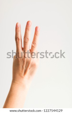 A hand showing three fingers (index finger, middle finger and ring finger) on white background for symbol that counting number three.