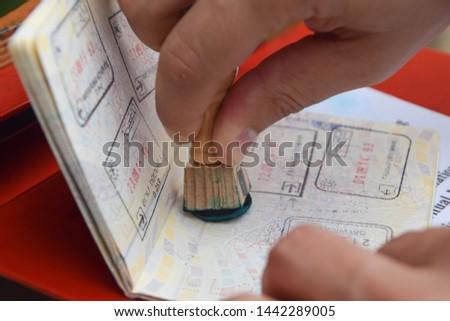 A hand stamping a passport #1442289005