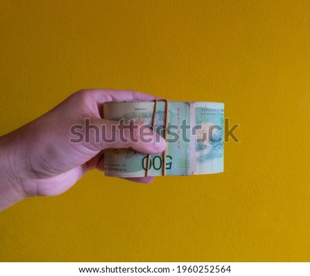 a hand that gives the feeling of handing over Argentine money with an elastic band and reverse bills in sight and details of the bill Photo stock ©