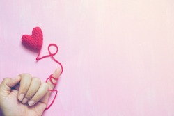 A hand that little finger bind with red yarn with crochet heart on painted pink canvas background