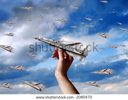 a hand throwing a paper plane to join others planes