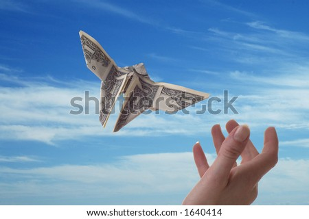 A hand trying to catch a dollar bill shaped like butterflies. A blue sky serves as the background.