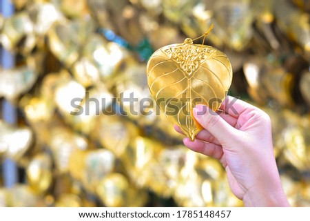 A hand was shown the artificial gold Bodhi leaf (write make a wish on it) at The Golden mountain temple ,Thailand Imagine de stoc ©