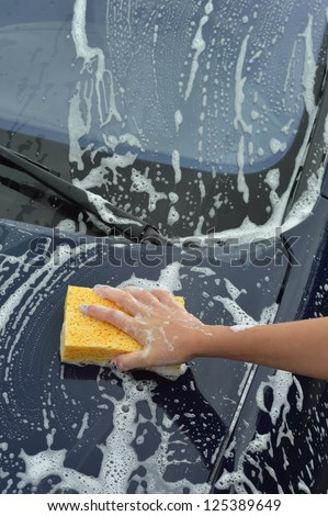 A Hand washing a car with a sponge