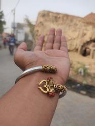 A hand wearing a bracelet of hindu God Lord Shiva.