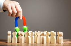 A hand with a magnet pulls green people out of crowd. Recruiting new workers, headhunters. Search for talented workers. Choose a candidate for work, competition for post. Promising specialists.