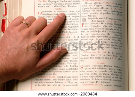 a hand with finger pointing a phrase on an old bible