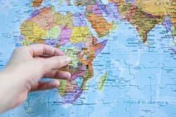 A hand with the final piece of the puzzle putting it in place on a global map of the planet with all counties listed