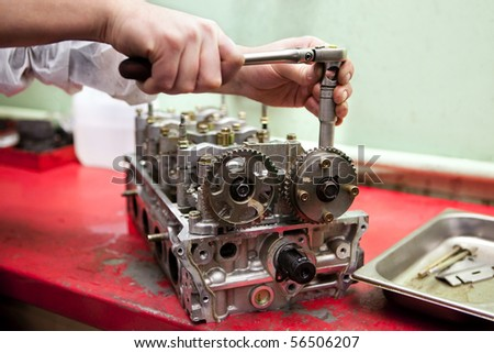 a hand with the wrench is repairing an engine