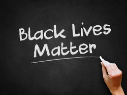 A hand writing 'Black Lives Matter' on chalk board for social issue concept design theme.