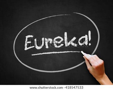 A hand writing 'Eureka!' on chalkboard.