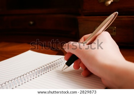 A hand writing on a pad of paper on a wooden desk.