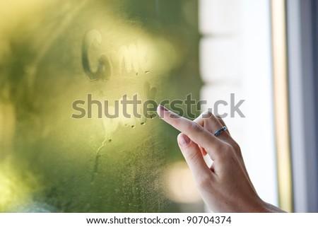 A hand writing on window