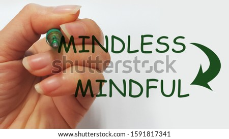 A hand writing the word Mindless with an arrow to Mindful. To depict Mindfulness concept