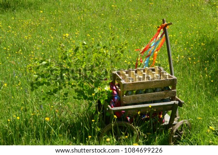A handcart with a blanket, a beer box, colorful ribbons on a wonderful spring meadow for fathers day - Shutterstock ID 1084699226