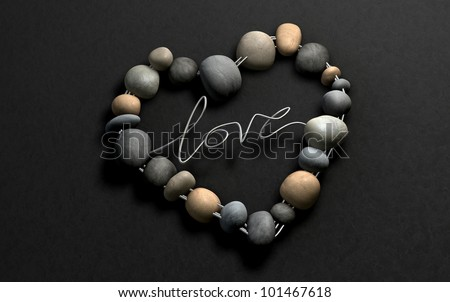 A handcrafted heart shape made out of wire and stones with the word  Love spelled out on a stone background - stock photo