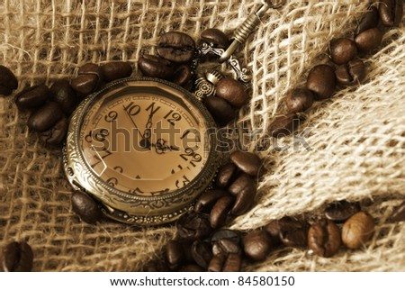 A handful of coffee beans on some burlap with an antique pocket watch.