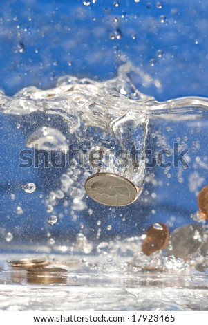 A handful of coins dropping into a pool of water.