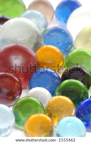 "A handful of multi-colored transparent ""clearie"" marbles on a white background."