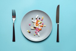 A handful of pills, capsules and multi-colored tablets on a plate next to cutlery. Taking medication. Pills instead of food. The concept of vitamins instead of food