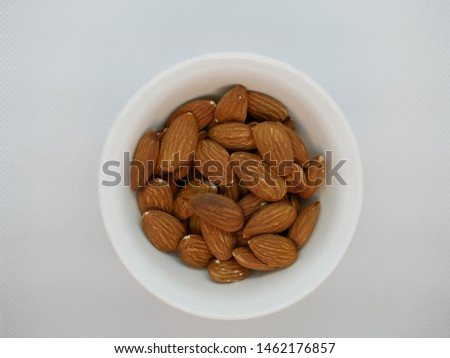 a handful of roasted almonds in a white porcelain plate on a white background. Natural vitamin. Healthy food. vegetarian food.