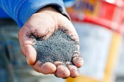 A handful of sand (basalt) grits for sandblasting or abrasive blasting of metal surfaces.
