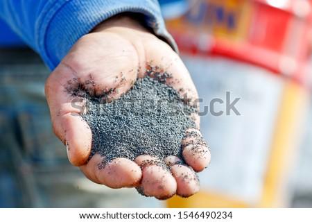 A handful of sand (basalt) grits for sandblasting or abrasive blasting of metal surfaces. ストックフォト ©